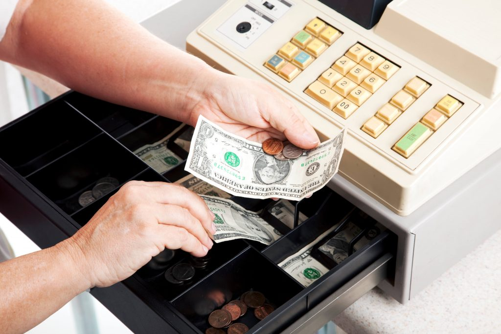 hands getting change from cash register